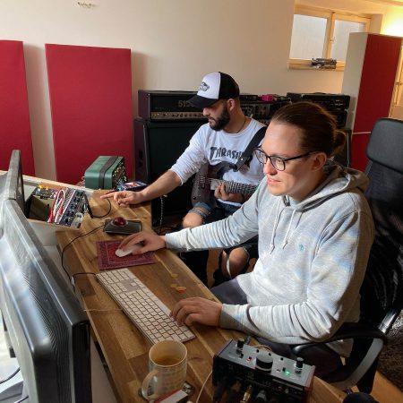 Gitarrist Ben (links) und Producer Emil (rechts) schaufeln unter Tage Gitarrenspuren übereinander.